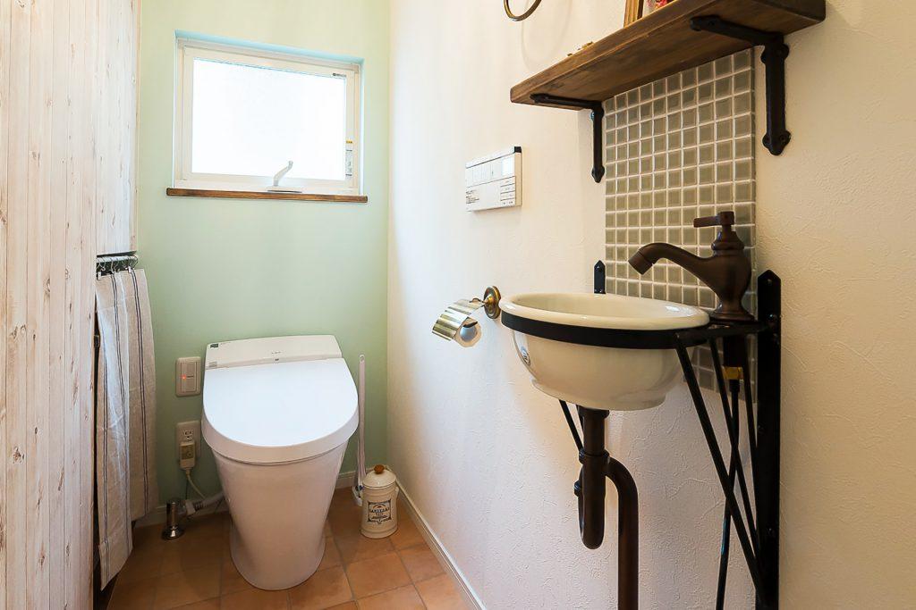 溢れる想いを優しくまとめた家の緑の壁のトイレ